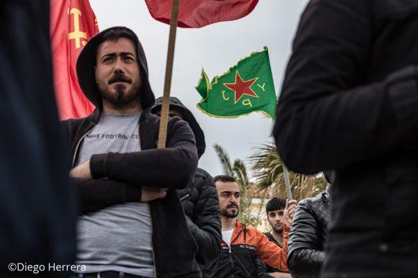 Un hombre sostiene una bandera de la YPJ durante una manifestación por las calles de Lavrio