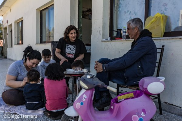 Una familia compartiendo un te y jugando con los niños